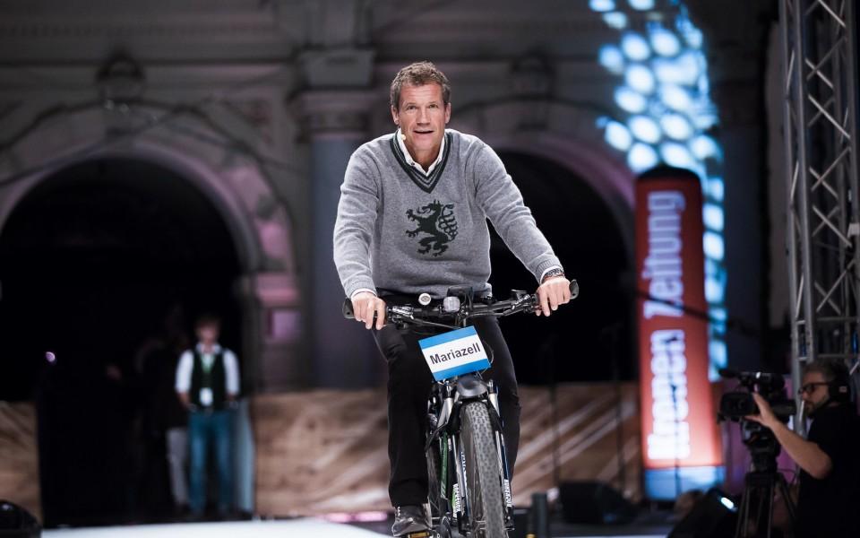 """Moderator Armin Assinger kam mit dem Rad zur """"Pracht der Tracht"""" und drehte damit eine Runde am Laufsteg (Foto Ivents/Marija Kanizaj)"""