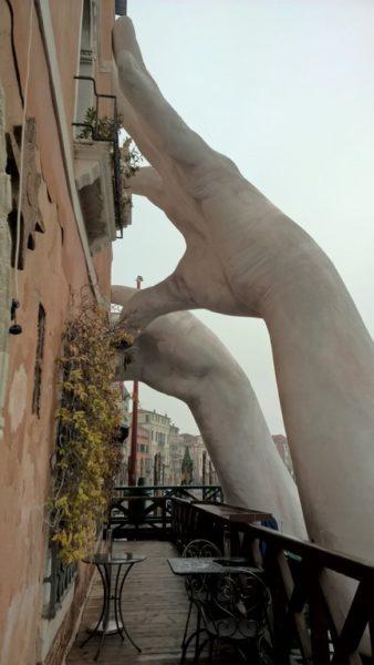 Ein Hingucker beim Ca Sagredo Hotel sind die beiden weißen Hände, die aus dem Canal Grande ragen und die Hotelfassade zu stützen scheinen (Foto Reinhard Sudy)