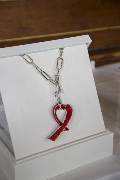 Zu dem Award gehören eine atemberaubende, mit funkelnden Swarovski Kristallen besetzte Halskette in Form einer roten Schleife sowie eine Spende von 100.000 Euro (Foto Swarovski)