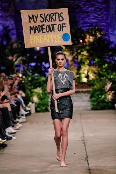 """Designerin Marina Hoermanseder präsentierte während der Berliner Fashion Week ihre Autumn/Winter Kollektion 20/21. Darunter auch ihr berühmter Strap-Skirt, der ab sofort auch in veganem Leder aus Ananasblättern erhältlich ist. Ein Model trug ein Schild mit der Aufschrift """"My skirt ist made out of Pineapple"""". (Foto Stefan Kraul)"""